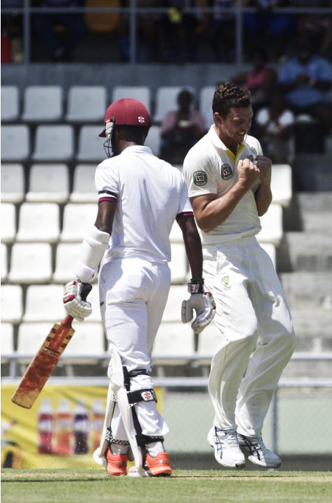 Australia opening bowler Josh Hazlewood, right, celebrates after taking the wicket of West Indies' opening batman Kraigg Brathwaite, left, who was caught by Australia's Brad Haddin for 10 runs