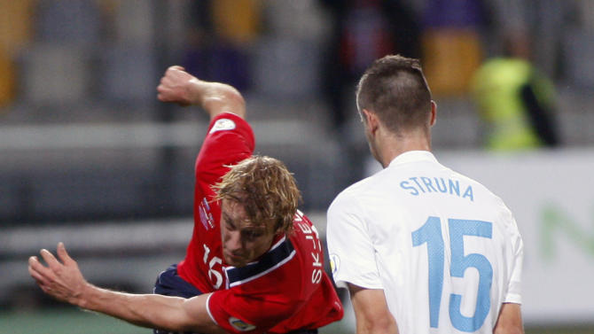Norway's Per Ciljan Skjelbred, left,  is challenged by Slovenia's Andraz Struna during the 2014 World Cup group E qualifier soccer match between Slovenia and Norway in Maribor, Slovenia, Friday, Oct 11, 2013