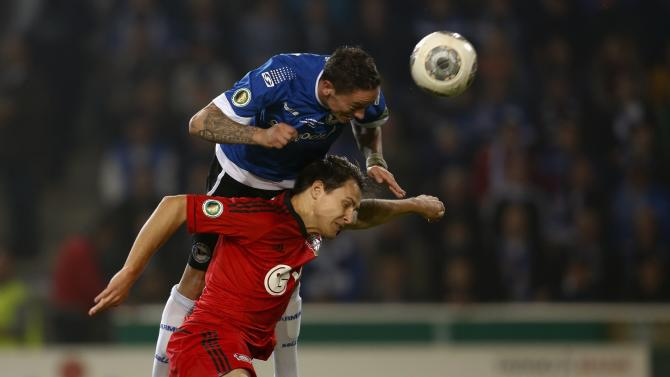 Bayer Leverkusen's Wollscheid and Arminia Bielefeld's Mueller jump for the ball during the second round of their German soccer cup match in Bielefeld