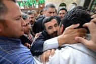 Iranian President Mahmoud Ahmadinejad (centre) kisses an Egyptian man during his visit to the Sayyeda Zeinab mosque in Cairo, on February 5, 2013. Egyptian President Mohamed Morsi has urged Syrian opposition groups to unify, as he addressed leaders of Islamic states at a summit that also tackled the battle against militants in Mali
