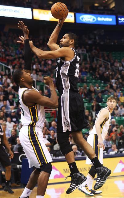 San Antonio Spurs' Tim Duncan, right, shoots the ball as Utah Jazz's Derrick Favors, left, defends in the first half of an NBA basketball game on Saturday, Dec. 14, 2013, in Salt Lake City