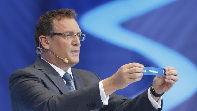"Valcke holds up the slip showing ""Colombia"" during the draw for the 2014 World Cup in Sao Joao da Mata"
