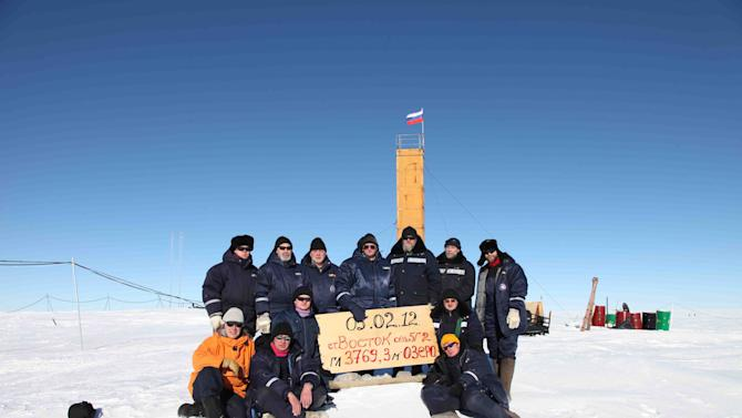 "In this Monday, Feb. 5, 2012 photo provided by Arctic and Antarctic Research Insitute of St. Petersburg,   Russian researchers at the Vostok station in Antarctica pose for a picture after reaching subglacial lake Vostok. Scientists hold the sign reading ""05.02.12, Vostok station, boreshaft 5gr, lake at depth 3769.3 metres."" The Russian team reached the lake hidden under miles of Antarctic ice on Sunday, a major scientific discovery that could provide clues for search for life on other planets. (AP Photo/Arctic and Antarctic Research Institute Press Service, )"