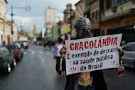 """A demonstrator holds a banner reading """"Cracolandia is an example of the failure of Brazilian public health policy"""" during a demonstration against paramilitary police's clean-up operation in the area called """"Cracolandia"""" (Crackland) in downtown Sao Paulo, Brazil on January 14"""