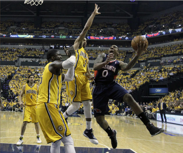 Atlanta Hawks' Jeff Teague shoots against Indiana Pacers' Roy Hibbert and George Hill (3) during the first half in Game 1 of an opening-round NBA basketball playoff series on Saturday, April 1