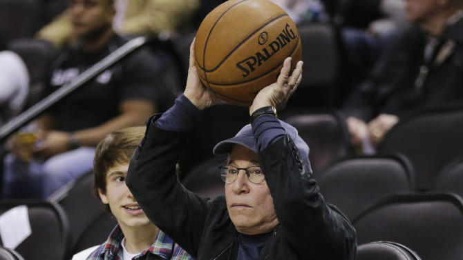 Musician Paul Simon returns a basketball as he attends an NBA basketball game between the San Antonio Spurs and the New York Knicks, Thursday, Jan. 2, 2014, in San Antonio. (AP Photo/Eric Gay)