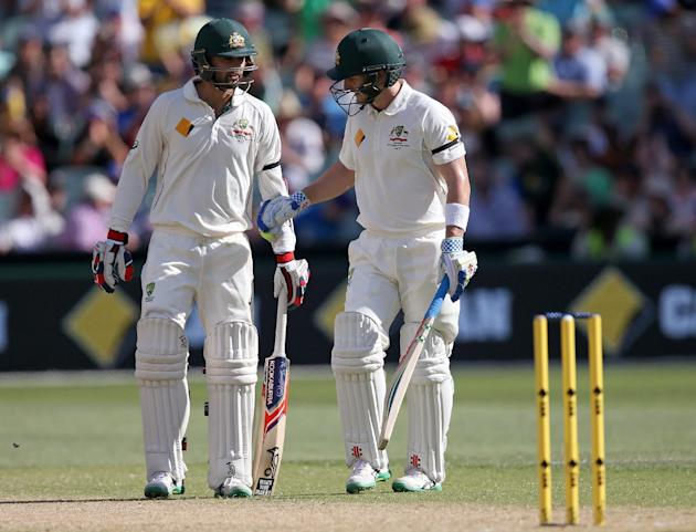 Australia's Peter Nevill, right, and batting partner Nathan Lyon meet mid-wicket during a change of ends while playing New Zealand in their cricket test in Adelaide, Saturday, Nov. 28, 2015. This