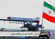 An image grab taken from Iran's Al-Alam TV on January 28, 2013, shows the Iranian flag at an unknown location flying in front of a capsule containing a live monkey which the Tehran-based Arab-language channel said they sent up into space and later retrieved intact. Iran successfully sent a monkey into orbit, Defence Minister Ahmad Vahidi tells state television