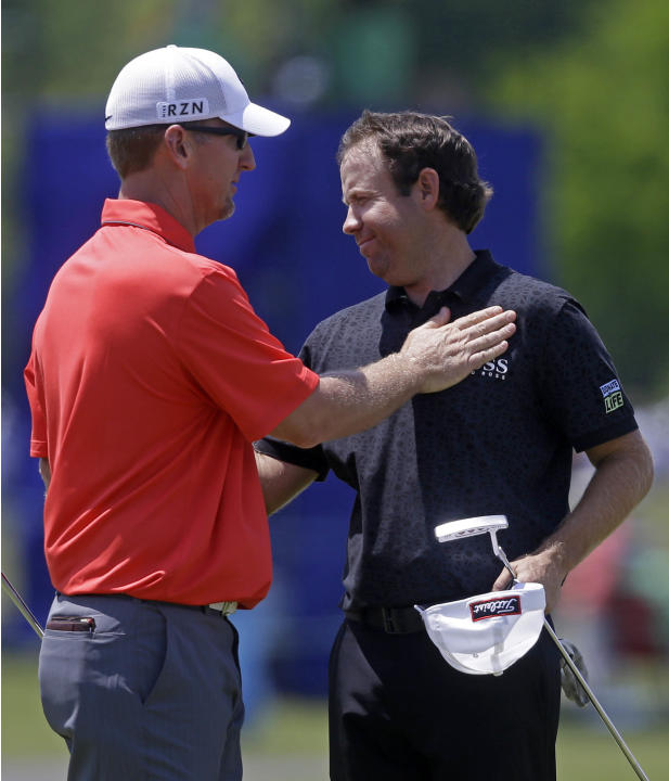 Erik Compton, right, is congratulated by David Duval after the two finished the day on the ninth green during the opening round of the Zurich Classic golf tournament at TPC Louisiana in Avondale, La.,