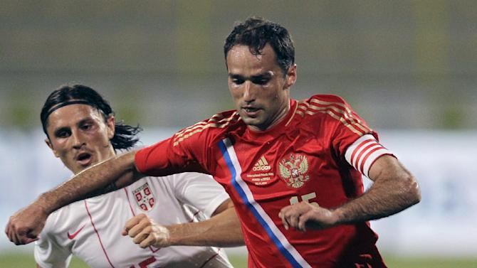 Serbia's Ljubomir Fejsa, left, fights for the ball with Russia's Roman Shirkov during a friendly match Dubai, United Arab Emirates, Friday Nov. 15, 2013