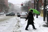 A pedestrian shelters under an umbrella as he crosses the street during a winter nor'easter snow storm in Lawrence, Massachusetts January 2, 2014. REUTERS/Brian Snyder