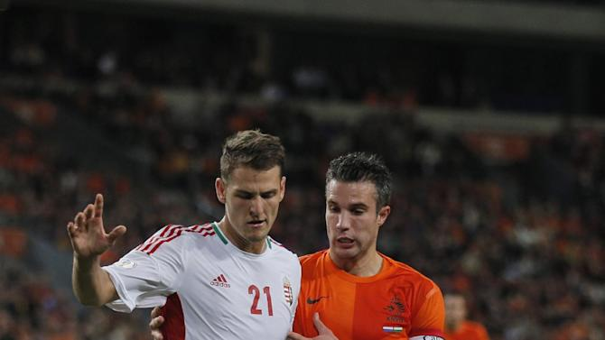 Netherlands' Robin van Persie, right, and Hungary's Zsolt Korcsmar, left, vie for the ball during the Group D World Cup qualifying soccer match between Netherlands and Hungary, at ArenA stadium in Amsterdam, Netherlands, Friday Oct. 11, 2013. The Netherlands won the match with a 8-1 score