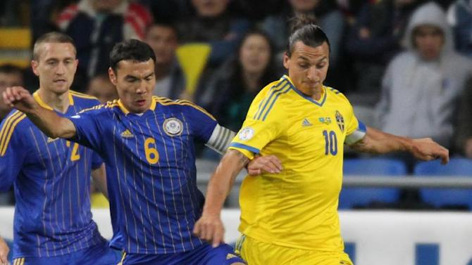 Kazakhstan's Kairat Nurdauletov, centre, and Sweden's Zlatan Ibrahimovic, right, fight for the ball during their World Cup group C qualifying soccer match in Astana, Kazakhstan, Tuesday, Sept. 10, 2013. (AP Photo)