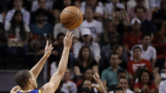 Golden State Warriors' Stephen Curry (30) shoots a 3-point basket as Miami Heat's Norris Cole, right, defends during the first half of an NBA basketball game, Thursday, Jan. 2, 2014, in Miami
