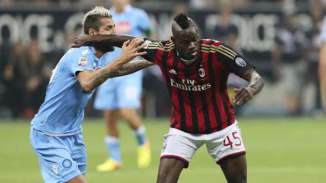 AC Milan forward Mario Balotelli, right, holds back Napoli midfielder Valon Behrami, of Switzerland, during the Serie A soccer match between AC Milan and Napoli at the San Siro stadium in Milan, Italy, Sunday, Sept. 22, 2013