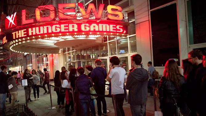 """Fans line up to see the midnight shows of """"The Hunger Games,"""" at the 34th Street Loews AMC Theatre, Thursday, March 22, 2012, in New York. The film, about children who are forced to compete in a live televised death match in the not-too-distant future, is based on the popular young adult book series by Suzanne Collins. (AP Photo/John Minchillo)"""