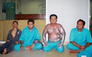 Image provided by the Malaysian Maritime Enforcement Agency shows passengers rescued from an overturned boat off the Johor coast waiting at the maritime office, on August 2, 2013. The rescuers on Sunday said hopes were fading for 40 Indonesians still missing