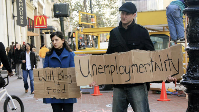 Unemployed people hold signs along Market Street in San Francisco