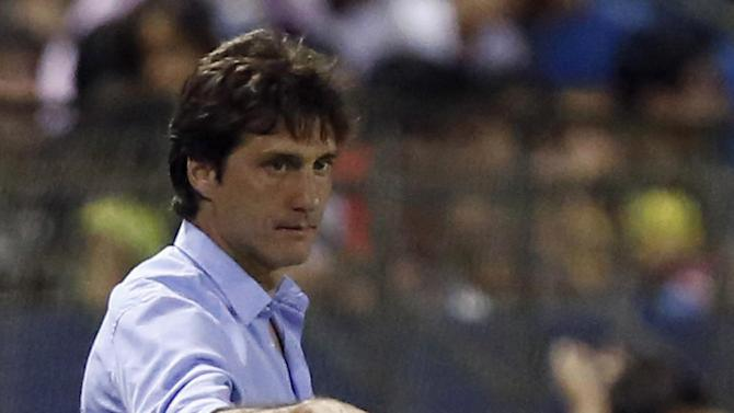 Guillermo Barros Schelotto, coach of Argentina's Lanus, dribbles the ball on the sidelines of a Copa Sudamericana soccer game with Paraguay's Libertad in Asuncion, Paraguay, Thursday, Nov. 21, 2013