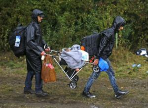 Two migrants carry a child in a pram as they walk towards…