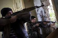 Rebel fighters aim their weapons at regime forces on the front line in the Old City of Aleppo, on December 21, 2012. More than 44,000 people are estimated to have been killed since the eruption in March 2011 of the uprising that morphed into an armed insurgency.