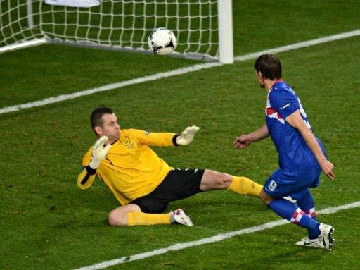 Croatian forward Nikica Jelavic (R) scores a goal against Irish goalkeeper Shay Given