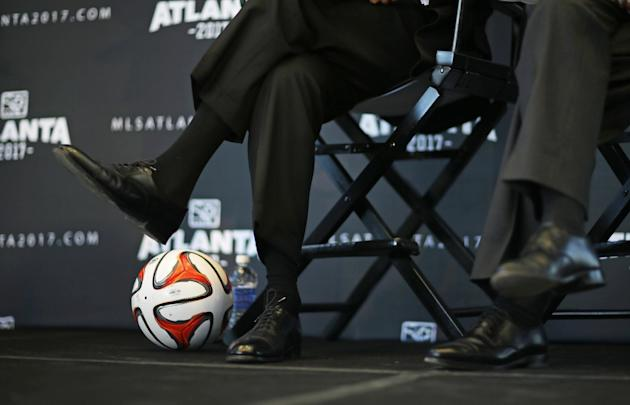 A soccer ball rests by the feet of Atlanta Falcons owner Arthur Blank, left, and Frank Poe, right, executive director of the Georgia World Congress Center Authority, during a news conference announcin
