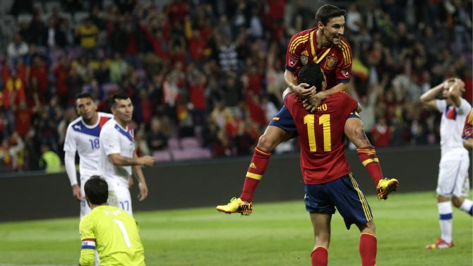 Spain's Jesus Navas, top, celebrates his goal with teammate Pedro Rodriguez (11), after he scored their second goal during a friendly soccer match between Spain and Chile at the Stade de Geneve stadium, in Geneva, Switzerland, Tuesday, Sept. 10, 2013