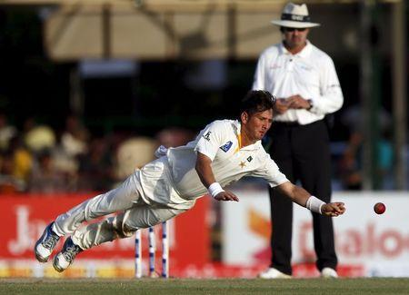 Pakistan's Shah dives to stop the ball hit by Sri Lanka's Sangakkara during the first day of their second test cricket match in Colombo