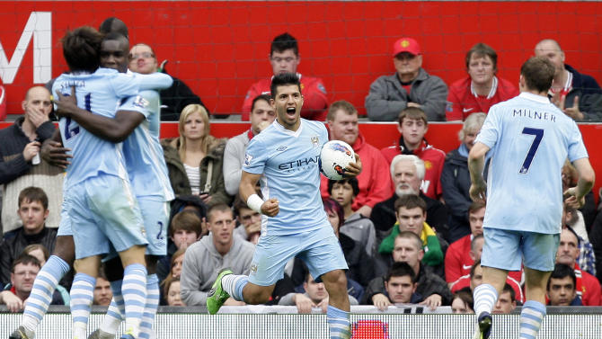 Manchester City's Sergio Aguero, centre, celebrates with teammates after his first goal during his team's 6-1 win over Manchester United in their English Premier League soccer match at Old Trafford Stadium, Manchester, England, Sunday Oct. 23, 2011. (AP Photo/Jon Super)