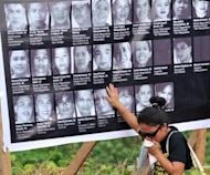 File photo of a relative of one of the 57 victims of the 2009 Maguindanao massacre cries as she touches a collage of photos of the victims at the site of the killings in Ampatuan. Hired assassins are stalking witnesses to the massacre in which a political warlord allegedly led the slaughter of 57 people, victims' relatives and a rights group said almost two years into a complex trial