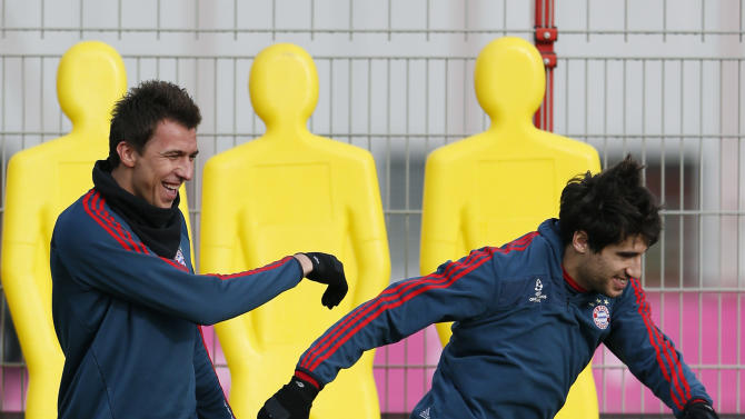 Bayern's Mario Mandzukic of Croatia, left, jokes to team mate Javier Martinez of Spain as he arrives for a last training session prior the Champions League group D soccer match between FC Bayern Munich and Manchester City, in Munich, southern Germany, Monday, Dec. 9, 2013. Munich will face Manchester Tuesday