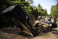 Thai police officers inspect the vehicles of six Buddhist huntsmen who were killed by suspected Muslim militants in Thailand's restive southern province of Narathiwat