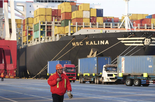 FILE - In this Tuesday, April 8, 2014 file photo, a worker walks past a container vessel docked in Qingdao port in east China's Shandong province. China's economic growth slowed to 7.4 percent