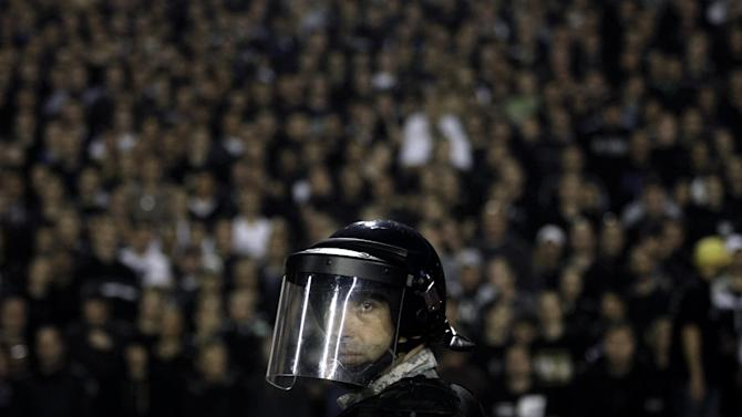 A member of the Serbian Gendarmerie secures the pitch during a Serbian soccer league fixture between arch rivals Red Star and Partizan Belgrade in Belgrade, Serbia, Saturday, Nov. 2, 2013. Marred with bouts of fan violence and frequent match fixing scandals, Serbian soccer seems to be in deep crisis, resulting with the national team failing to qualify for the 2014 World Cup