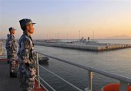 Chinese naval soldiers stand guard on China's first aircraft carrier Liaoning, as it travels towards a military base in Sanya, Hainan province, in this undated picture made available on November 30, 2013. REUTERS/Stringer