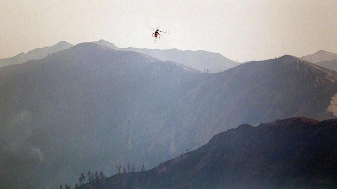 A type 1 sky crane flies with mountains as a backdrop while battling the Beaver Creek Fire, Monday Aug. 19, 2013. (AP Photo/Idaho Statesman, Kyle Green)