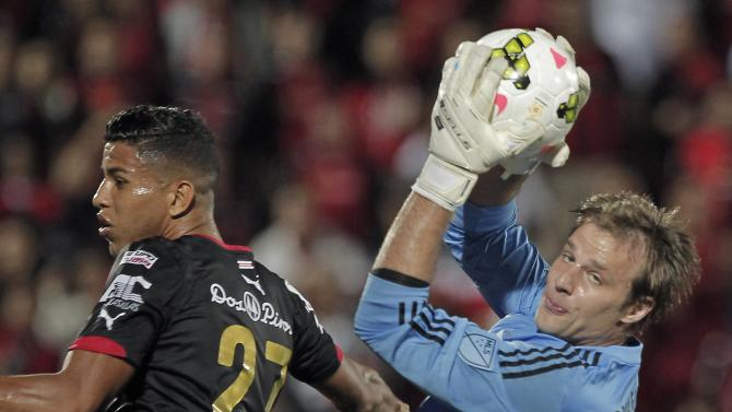 Goalkeeper Andrew Dykstra of  D.C. blocks the ball near Johan Venegas of Liga Deportiva Alajuelense during their CONCACAF Champions League soccer match in Alajuela