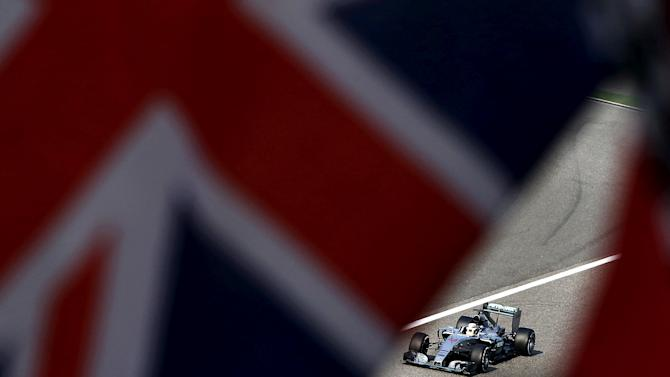 FILE PHOTO -  Mercedes Formula One driver Hamilton of Britain is seen behind British national flags in the last lap of the Chinese F1 Grand Prix at the Shanghai International Circuit