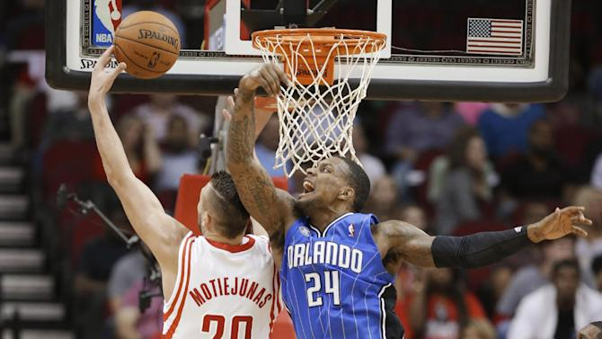 Houston Rockets' Donatas Motiejunas (20) reaches for the rebound ahead of Orlando Magic's Romero Osby (24) during the second half of a preseason NBA basketball game Wednesday, Oct. 16, 2013, in Houston
