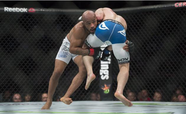 Demetrious Johnson, left, from the United States, lifts Kyoji Horiguchi, from Japan, during their UFC 186 mixed martial arts flyweight title fight in Montreal, Saturday, April 25, 2015. (Graham Hughes