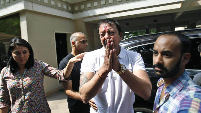 Indian Bollywood actor Sanjay Dutt, center, gestures to the media after he broke down during a press conference as his sister Priya Dutt, left, stands next to him at his residence in Mumbai, India, Thursday, March 28, 2013. Dutt said he has not sought pardon for a 1993 weapons conviction and will serve his prison sentence as ordered by India's Supreme Court. Dutt broke his silence a week after the court sentenced him to five years in prison for illegal possession of weapons supplied by Mumbai crime bosses linked to a 1993 terror attack that killed 257 people.(AP Photo/Rafiq Maqbool)
