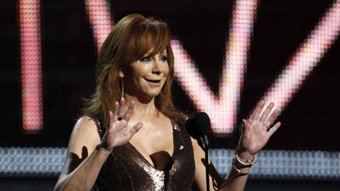 FILE - In this Sunday, Feb. 12, 2012 , file photo, Reba McEntire speaks onstage during the 54th annual Grammy Awards on in Los Angeles.  More than 20 years after a plane crash that killed seven members of her band and her tour manager, Reba McEntire  has come a long way since divorcing her first husband and firing her manager in the late '80s because they didn't believe she could go any farther in the male-dominated country music industry. McEntire is now a member of the Country Music Hall of Fame, has sold more than 55 million albums worldwide, and charted 63 top 10 hits.  (AP Photo/Matt Sayles, File)