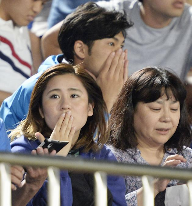Japanese soccer fans react to a strong earthquake as they watch a J-League soccer match between the Shonan Bellmare and the Sanfrecce Hiroshima at BMW Stadium in Hiratsuka, southwest of Tokyo Saturday