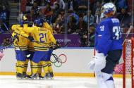Sweden's Daniel Sedin (obscured) is surrounded by his linemates celebrating his goal as Slovenia's goalie Robert Kristan looks on during the third period of their men's quarter-finals ice hockey game at the 2014 Sochi Winter Olympic Games, February 19, 2014. REUTERS/Brian Snyder