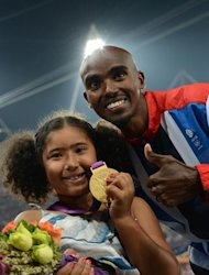 Britain's gold medalist Mohamed Farah and his daughter Rihanna pose on the podium of the men's 5000m at the athletics event of the London 2012 Olympic Games on August 11, 2012 in London. AFP PHOTO / JOHANNES EISELE
