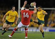 Australia's Will Genia from (right) kicks ahead during the second rugby union Test against Wales in Melbourne on June 16. Australia's Mike Harris kicked a penalty under huge pressure after the full-time siren to give the Wallabies a 25-23 win and break Welsh hearts