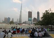 "Muslims break their fast during Ramadan last year outside a mosque near the Burj Khalifa tower in Dubai. The Gulf emirate's proposed ""Mall of the World"" will have a capacity of 80 mn visitors a year to become the ""largest in the world,"" said the statement, while its park will be ""30% bigger than Hyde Park of London."""