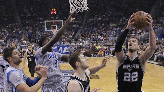 San Antonio Spurs' Tiago Splitter (22) goes up for a shot against Orlando Magic's Nikola Vucevic, left, and Dewayne Dedmon (3) during the first half of an NBA basketball game, Wednesday, April 1, 2015, in Orlando, Fla. (AP Photo/John Raoux)