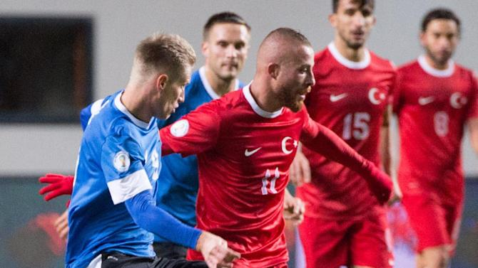 Estonia's Tarmo Kink, left,  fights for the ball with Turkey's Gokhan Tore during their World Cup Group D qualifying soccer match in Tallinn, Estonia, Friday, Oct. 11, 2013